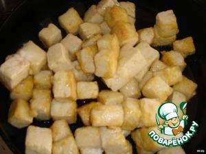 Тофу порезать кубиками, обвалять в крахмале и обжарить на растительном масле до золотистого цвета.