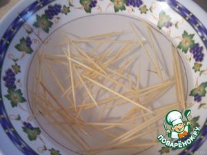 На картофель кладём лук, потом бекон и закрепляем зубочисткой.