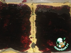 Противень выстелить пергаментной бумагой, смазать маслом,   Выложить тесто.   Выпекать в духовке при температуре 200С - 8 минут.   Корж разделить на 2 части,смазать черничным вареньем.