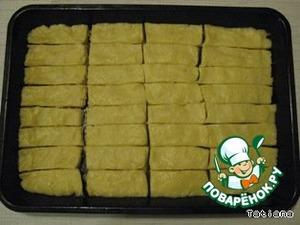 Выложить тесто на смазанный маслом противень, разрезать на