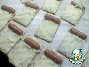 Намазать на каждый хлебец картофельное пюре.    Положить на каждый хлебец, намазанный пюре, половинку сосиски (чуть ближе к середине) и дать постоять в таком виде минут 5-7.