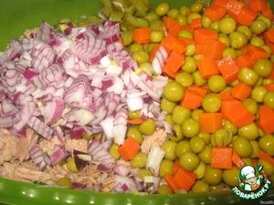 С горошка и моркови сливаем жидкость и отправляем к тунцу, лук с корнишонами туда же.