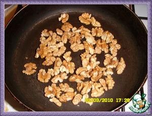 Обжарить орехи на сухой сковороде и крупно порубить ножом. Очистить мандарины от кожи, разделить на дольки, снять пленку. Разложить салат по тарелкам, добавить орехи и мандарины, посыпать перцем.