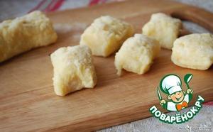Разделить тесто на несколько частей и скатать колбаски толщиной 2 см. Порезать на небольшие кусочки.