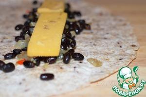 Немного остывшую начинку выложите на тортильи, сверху ломтики сыра (или натертый), сформируйте буррито краями внутрь, чтобы начинка не выпадала.