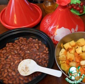 В сковороду тажина выложить консервированную фасоль вместе с жидкостью (или можно выложить замоченный на ночь горох или нут).