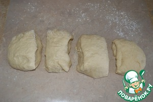 Когда тесто подойдет, его нужно обмять и разделить на 4 части.