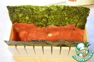 Лист нори выложить в форму для роллов блестящей сторонй вниз. Распределить красную рыбу-кижуч равномерно по поверхности нори.