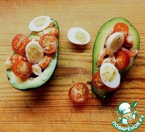 Авокадо разрезаем на две части, удаляем косточку. Сбрызгиваем оставшимся лимонным соком, чтобы мякоть не темнела. Выкладываем в половинки авокадо орехи, раковые шейки, помидоры черри и перепелиные яйца.