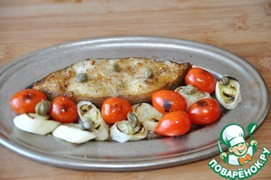 Через 10 минут после начала запекания достаём рыбу из духовки, очень быстро кладём рядом с рыбой обжаренные помидоры и лук, смазываем кисточкой оливковым маслом. Рыбу и овощи посыпаем майораном, кладём каперсы и отправляем назад в духовку ещё на 10 минут.