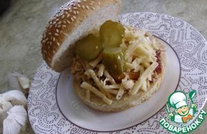 Берем булочку для гамбургеров, разрезаем на две половины, на одну выкладываем курицу с соусом, посыпаем сыром и ложим ломтики огурчиков.   Приятного аппетита!