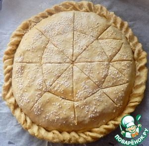 Раскадываем последнюю часть теста, накрываем ей начинку, свободные края первого пласта заворачиваем к пирогу как косичку, делая польчиками узор. Поверхность смазываем водой посыпаем кунжутом, делаем в верхнем слое теста надрезы, до начинки. Даем постоять 10 минут в теплом месте затем ставим выпекатьсяв духовку на 35-40 минут
