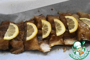 Lay the baking paper on the baking sheet and lay the fish pieces on top lay the slices of lemon and fold the parchment. Put bake in a preheated 180 degree oven for 20 minutes.