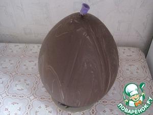 Для приготовления яйца обливаем воздушный шарик растопленным шоколадом, даем застыть. Шарик прокалываем, вынимаем сверху через отверстие.
