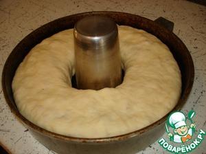 Сворачиваем плотный рулет, концы соединяем в кольцо и выкладываем в смазанную маслом форму. Накрываем плёнкой и оставляем для подъёма.