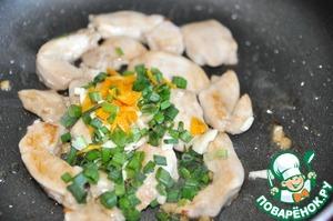 Кладём назад курицу на сковородку.    Добавляем нарезанные зелёный лук, чеснок и цедру.