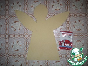 The finished dough roll out the layer cut in the form of an angel with wings and put on the Mat for baking