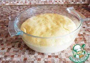 Когда тесто поднимется, разделить его на четыре части.   Одну часть раскатать на бумаге для выпечки и с помощью подходящего блюда вырезать из раскатанного теста овал.