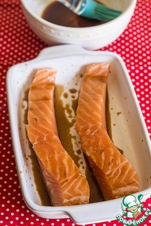 Подготовить лосось. Выложить его в блюдо для запекания.      Хорошо смазать лосось маринадом. Залить им рыбу. Оставить мариноваться около 30 минут.