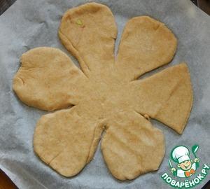 Из указанного количества ингредиентов получается один большой круглый пирог 28 см, частично закрытый. Я предлагаю Вам очень красивую праздничную формовку, которая очень проста в исполнении. Когда тесто подошло, отделяем от него кусочек чуть больше половины. Раскатываем в круг 26см, если получилось не очень ровно его всегда можно подрезать. Выкладываем пласт на противень, застеленный пекарской бумагой. Делаем 5-6 надрезов примерно на 2/3 радиуса, из каждого сегмента формируем лепесток, подгибая острые уголки и немного вытягивая край лепесточка
