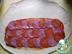 Готовое тесто хорошо обмять и выпустить лишний воздух. Раскатать в поперечный овал, толщиной 3-5 мм. Смазать чуть больше половины кетчупом, уложить колбасу (у меня готовая нарезка-кусочки очень тоненькие)