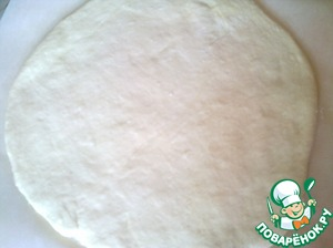The dough came, start with making the pie. Divide the dough into two parts. Roll out one part into a circle with a diameter of 30 cm and put on parchment paper, greased. Paper use in order to make it easier to move the finished product into the baking dish