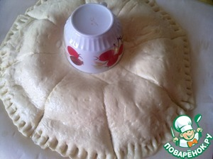 Cover the filling with a second dough circle and fix the middle of the Cup. The edges of the cake crush with a fork so that during baking do not open. Cut the dough as shown in photo and wrenched every bit stuffed up.