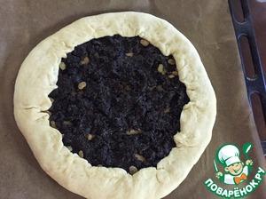 Делим тесто на 2 части. Одну часть раскатываем, раскладываем чернослив, края немного загибаем к центру пирога