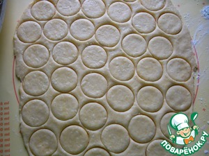 Lay out on a work surface, podpylennuyu with flour, and roll out to a thickness of 2-3 mm. Cut out circles using the stack (I have a 4.5 cm in diameter), which had previously been dipped in flour