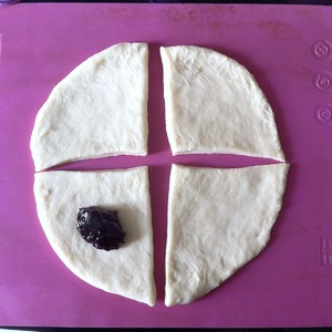 Roll out each portion into a cake and divide it into four segments. Spread on each segment about a teaspoon of thick jam. I have blackcurrant.
