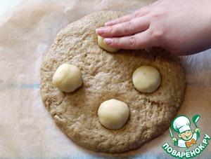 Подошедшее тесто еще немного месим, формируем из него круглый хлеб диаметром не больше 16 см, удобно сделать это сразу на пекарской бумаге, у меня получился диаметр 20см. и хлеб получился низкий. Марципан делим на 4 части скатываем шарики, укладываем на тесто придавливая их. Смазываем сверху молоком, ставим выпекаться на 25-30 минут.