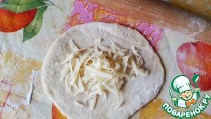 С помощью скалки тесто раскатать в пласт и выложить натёртый сыр.