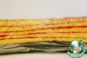 Сложите полосы друг на друга, как на фото.      Накройте бисквит пищевой пленкой и поставьте в морозильную камеру для застывания на 40- 60 минут.