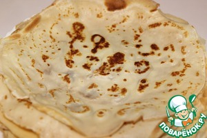 Bake thin pancakes, pouring the batter onto a hot frying pan, greased with vegetable oil and fried on both sides.