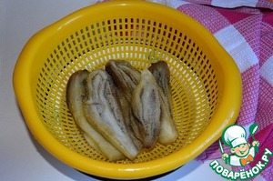 """Достать баклажаны из духовки, обдать холодной водой и снять с них кожицу.   Сложить баклажаны в дуршлаг (я их разрезала пополам вдоль) и посыпать солью, чтобы """"ушла"""" горечь. Оставить так баклажаны на некоторое время, примерно минут на 20. Затем промыть, смыть соль и дать стечь воде."""
