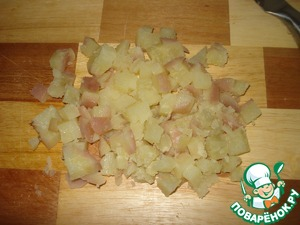 Boil potatoes in their skins, peel and cut into cubes.