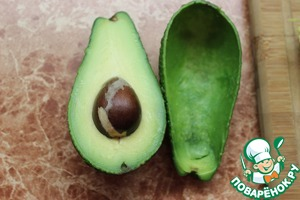 Take the avocado, cut neatly into 2 parts, remove the pit and spoon out the pulp. Skins are not thrown away, they will serve as plates for the salad.