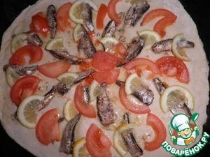 On the dough spread minced through a garlic press.  Then place the sprats, sliced tomatoes and lemon.