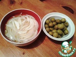 Первым делом поместим в глубокую миску луковицу, нашинкованную перьями, открываем банку оливок, сливаем рассол в лук, прикрываем пищевой плёнкой, и оставляем мариноваться.