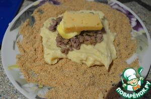 На тарелку высыпать сухари, на них выложить столовой ложкой картофельное пюре. Разровнять ложкой. Сверху выложить чайную ложку фарша, брусочек масла и сыра.