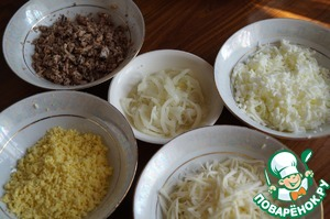 Prepare the ingredients for the salad: boiled eggs to grate on a coarse grater, separately the whites and yolks, cheese also RUB on a grater, grind the fish with a fork, cut onion into thin half rings and marinate in vinegar for 10 minutes.