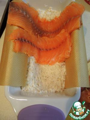 Филе лосося нарезать тонкими длинными ломтиками. Прямоугольную форму застелить пергаментом. Выложить половину рыбной массы. По всей длине продавить ложкой желобок. Поперек выложить немного внахлест ломтики лосося.