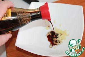 Чеснок давим с помощью чеснокодавилки. К нему добавляем соевый соус Kikkoman, яблочный уксус и растительное масло. Я сразу добавила немного сахара и соли.