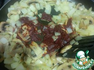 Освободите немного места посередине и положите томатную пасту. Немного ее прожарьте с грибами и луком. Буквально минуты 2-3.