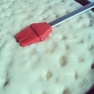 on top, your fingers, to make small holes.  mix the remaining oil with 2 spoons of water and spread with a brush the surface of the Focaccia