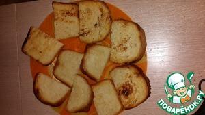 Румяные ломтики выкладываем на тарелку и разрезаем на порционные кусочки. Натираем зубчиком чеснока