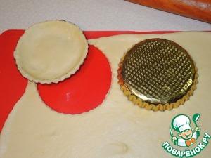 Тесто достать из холодильника, раскатать в пласт толщиной около 2мм, вырезать кружочки и уложить их в смазанные маслом формочки для выпечки, чтобы тесто закрывало дно и бока. Выпекать при 200 градусах 10-15 минут. Достать из духовки, накрыть полотенцем и полностью охладить.      Для украшения сливки взбить с сахарной пудрой.
