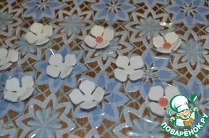 Сделать из мастики цветочки, дать хорошо им высохнуть. Серединки я заменила на серебрянные.