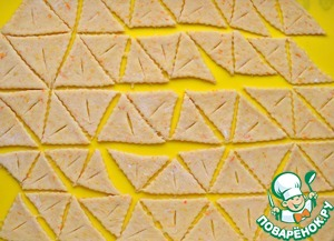 Table pagpalit with flour, roll out the dough thickness of 0.5 cm, and a Notched wheel to cut into strips with a width of 6 cm, cut them into triangles. In the center of each triangle to make an incision and pull through the corner.