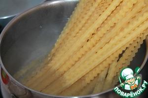 In salted water boil the pasta. It is best to take varieties of tagliatelle.
